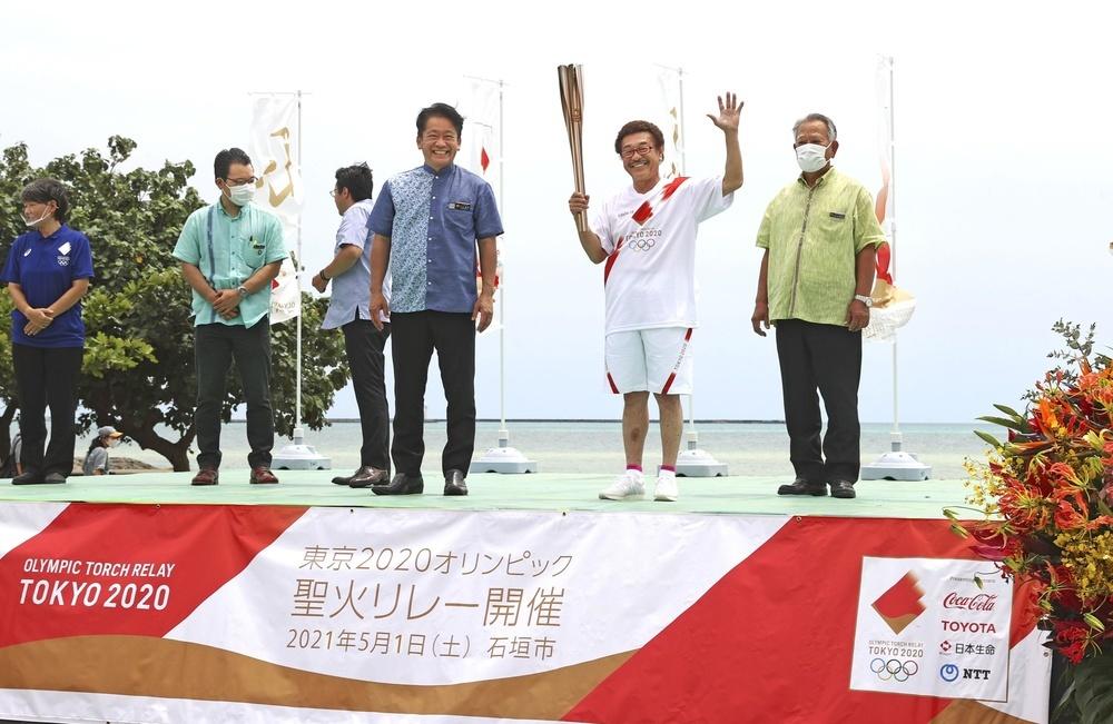 沖縄県石垣市で聖火ランナーを務め、ゴール会場でトーチを掲げる具志堅用高さん=1日午後