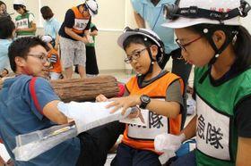 災害で負傷したとの想定で応急手当てを体験する子どもたち