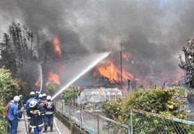 激しく燃える家屋に放水する消防士ら=26日午後0時35分、えびの市栗下