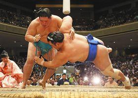 明生(左)がすくい投げで琴奨菊を破る 写真