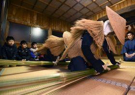 佐賀市蓮池町の見島地区の伝統行事「見島のカセドリ」で、住宅を訪問する前に、神社で青竹を打ち付けるカセドリ=9日夜(代表撮影)