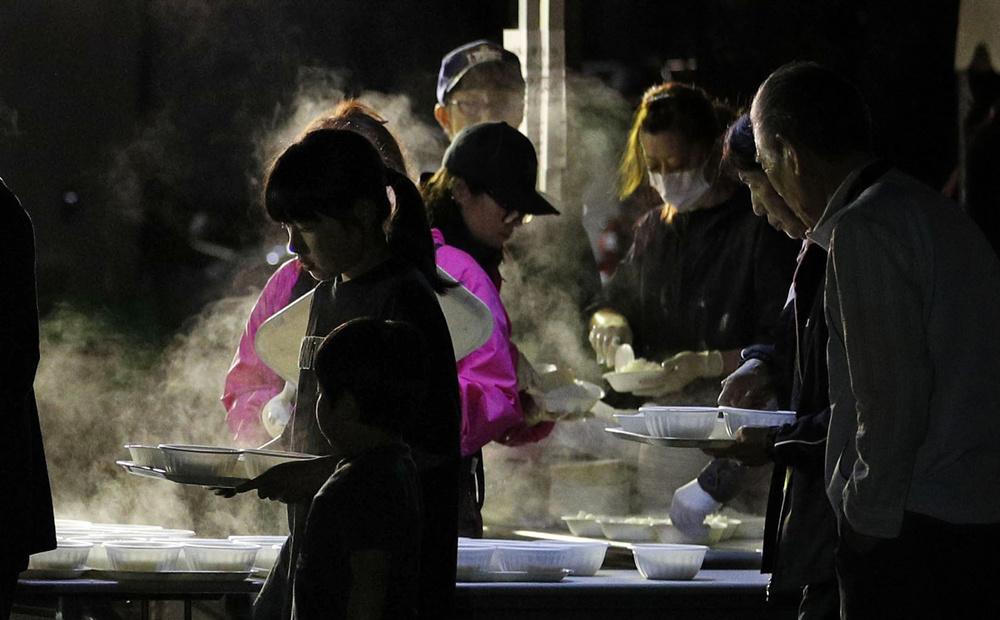 北海道厚真町の避難所で夕食の炊き出しを受け取る人たち。日が沈み冷え込む中、振る舞われた料理から湯気が立ち上った=10日夕