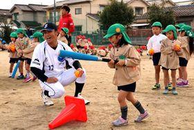 園児にバッティングを教える河野投手(手前左)