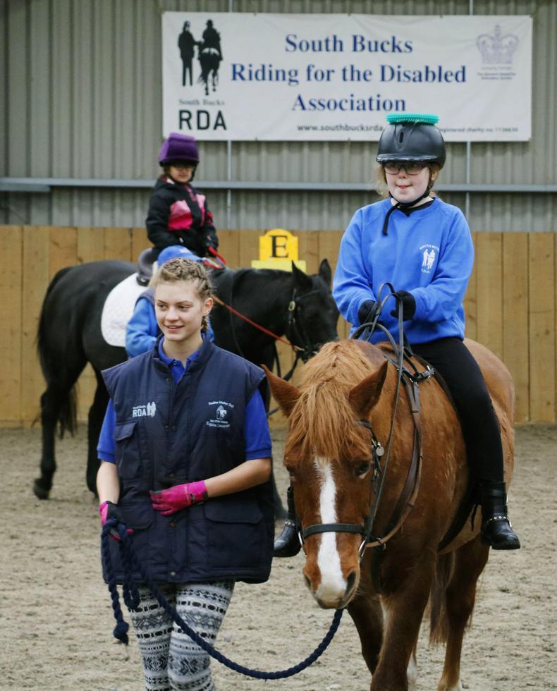 障害者乗馬クラブ「サウスバックス」でボランティアに付き添われ、馬術を学ぶ子どもたち。ヘルメットに輪を乗せてバランスを取る=ロンドン郊外(撮影・原田寛、共同)