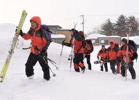 スキー用具などの装備品を手に入山する参加者