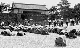 昭和天皇の「玉音放送」で終戦を知り、皇居前でひざまずく人たち。奥野誠亮氏らは玉音放送の直後、公文書焼却の指令書を地方の行政機関に届けた=1945年8月15日