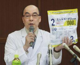 点滴袋を手に記者会見する下関医療センターの山下智省院長=21日午後、山口県下関市