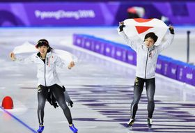 平昌冬季五輪のスピードスケート女子1000メートルで銀メダルを獲得し、日の丸を掲げる小平奈緒(右)と銅メダルの高木美帆=14日、韓国・江陵(共同)