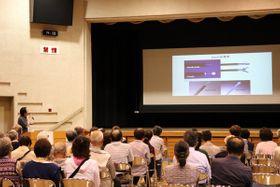 【黒田院長(左後方)の話を聞く参加者=桑名市常盤町の市総合福祉会館で】