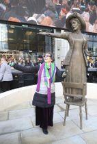 エメリン・パンクハースト像のポーズのまねをする、ひ孫のヘレンさん=14日、英マンチェスター(AP=共同)