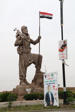 イラク北部の油田都市キルクークに立つイラク国旗を持ったクルド兵士の像。昨年の独立住民投票後にイラク軍が市を掌握するまではクルドの旗だった=5月(共同)
