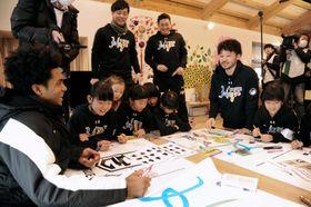 田臥勇太選手(右から2人目)らと一緒に横断幕にイラストを描く子どもたち=益城町