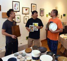 会場で自分の作品を手にする杉谷さん(左)、わしさん(中)、恵谷さん