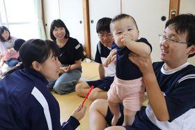乳児と触れ合う生徒たち=大村高
