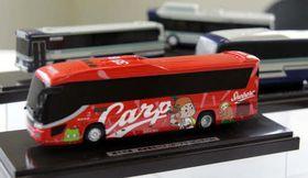 備北交通と「トイズ&ホビーむらかみ」が製作した、広島東洋カープのラッピングバスの模型(手前)
