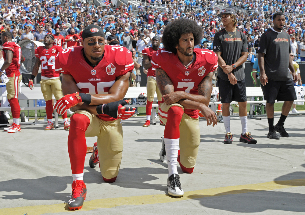 49ers時代の2016年9月の試合前、人種差別への抗議として国歌斉唱で膝をつくQBコリン・キャパニック(右)(AP=共同)