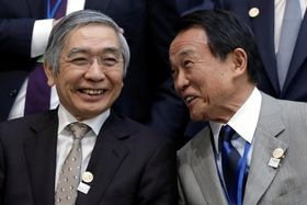 20カ国・地域(G20)財務相・中央銀行総裁会議の記念撮影で、日銀の黒田総裁(左)に話しかける麻生財務相=20日、米ワシントン(ロイター=共同)