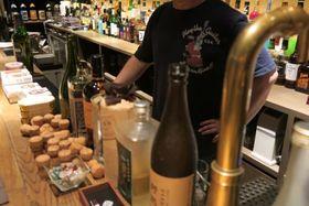 大阪・ミナミのバーで取材に応じた男性店主。「音楽を流せなくなるから、裁判で戦っちゃだめなんです」と諦め顔=2019年6月6日、大阪市中央区東心斎橋