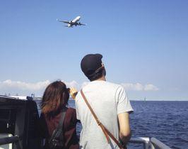 羽田空港付近を航行する船から、飛行機を見上げる乗客=4日