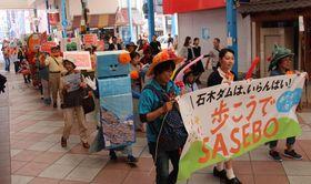 「石木ダムはいらない」と呼び掛けながらパレードする参加者=佐世保市下京町