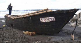 松前町の海岸に漂着した木造船=30日午前9時40分ごろ