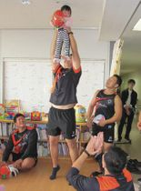 子どもを抱き上げるスピアーズの選手