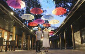 「ハルニレテラス」でライトアップされた色とりどりの傘を見上げる人たち=21日、長野県軽井沢町