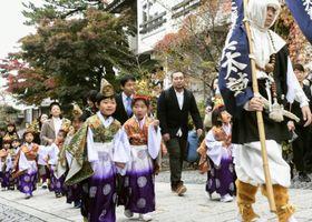 大山寺の参道を練り歩く色鮮やかな衣装をまとった稚児たち=24日午前、鳥取県大山町