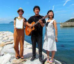 「あるある直島」を制作した福島節さん(中央)。右は妻の真希さん、左は漫画家のまつざきしおりさん=直島町