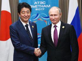 会談前にロシアのプーチン大統領(右)と握手する安倍首相=10日、ベトナム・ダナン(共同)