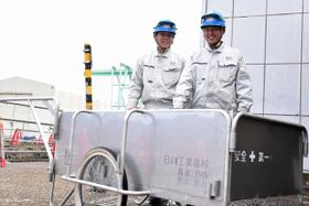 日向市内の民間企業で折り畳み式リヤカーを製作した黒木功弥さん(右)と黒木亮我さん