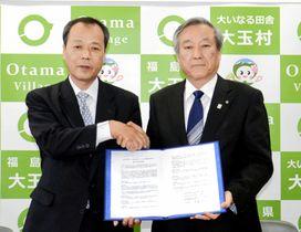協定書に調印し、握手を交わす押山村長(右)と渡辺社長