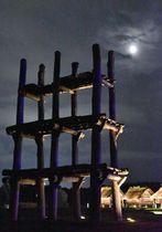 シンボル6本柱の大型掘立柱建物に懸かる名月。右奥は復元された掘立柱建物=24日午後7時43分、青森市の三内丸山遺跡