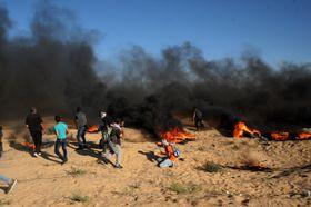 20日、パレスチナ自治区ガザ南部ラファのイスラエルとの境界付近で抗議デモをする人たち(UPI=共同)