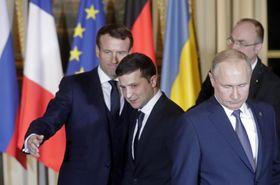 フランスのマクロン大統領(左)らの仲介で初会談したロシアのプーチン大統領(右)とウクライナのゼレンスキー大統領(中央)=9日、パリ(タス=共同)