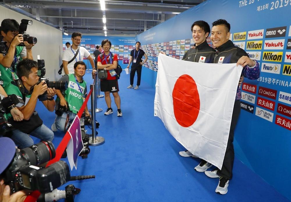男子シンクロ板飛び込みで東京五輪日本代表に決まり、日の丸を手に笑顔の寺内健(右)、坂井丞組=13日、韓国・光州(共同)