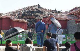 火災で焼けただれた北殿を見る観光客ら=12日午後、首里城・漏刻門