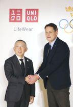 記者会見後に握手するファーストリテイリングの柳井正会長兼社長(左)とスウェーデン五輪委員会のピーター・レイネボCEO=24日午後、東京都江東区