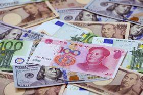 中国人民元の100元紙幣(中央)と100米ドル、1万円の紙幣など(共同)