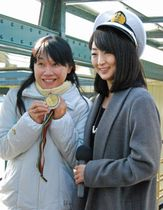ツアーの船内で、金メダルを持たせてもらい、岩崎恭子さん(右)と記念撮影する参加客