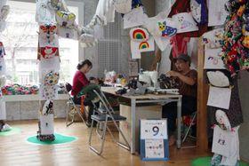 古着を素材にしたぬいぐるみに囲まれる、参加アーティストの阿部泰輔さん(右)=横浜市中区