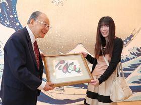 2万人目の来場者となり、出口会長(左)から記念品を受け取る重松さん=長崎市、県美術館