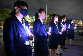 平和宣言を発表し、夕闇の中でペンライトを振る実行委のメンバー(撮影・天畠智則)