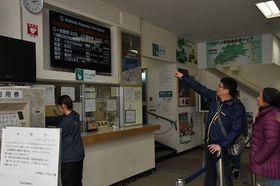 運休の知らせを確認する観光客=21日、青森市の八甲田ロープウェー山麓駅