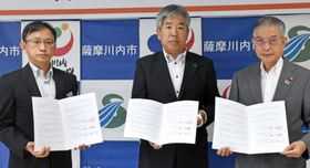 立地協定書に調印したイタックスの岩神徹也社長(中央)と岩切秀雄市長(右)ら=薩摩川内市役所