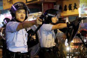「逃亡犯条例」改正案の撤回などを求めるデモ隊に向け、拳銃を構える警察官=25日、香港(ロイター=共同)