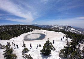 青空の下、雪が解けて現れた「八幡平ドラゴンアイ」=18日、八幡平山頂付近の鏡沼