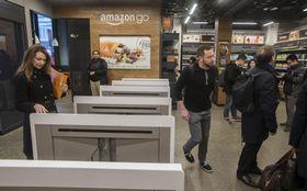 スマートフォンを自動改札機に似たゲートにかざして入店するレジなしの食品店「アマゾン・ゴー」=22日、シアトル(ゲッティ=共同)