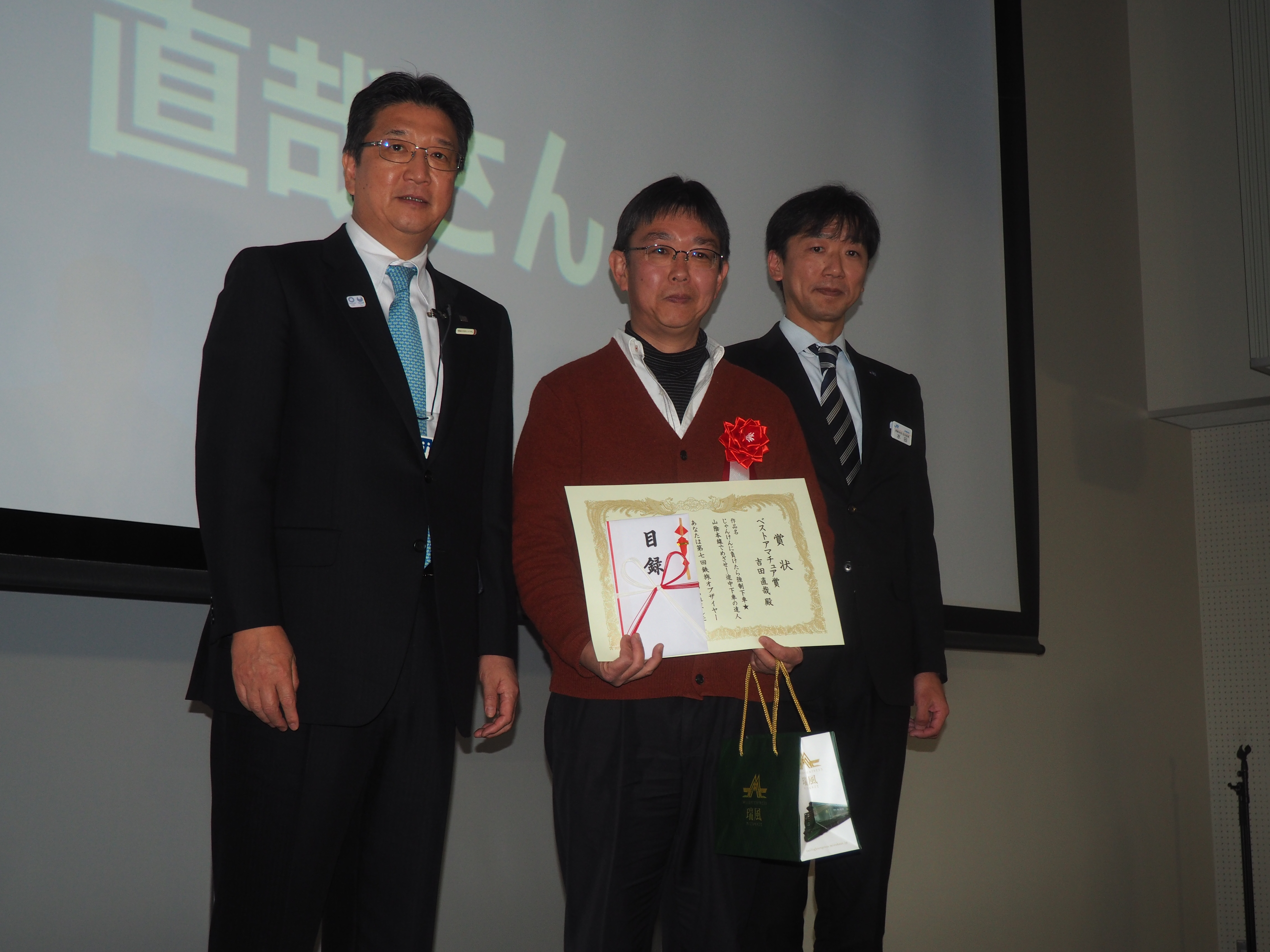 2017年度の「鉄旅オブザイヤー」授賞式で、「ベストアマチュア賞」を受けた吉田直哉さんさん(真ん中)とJTBの高橋広行社長(左)ら=2月7日、さいたま市の鉄道博物館