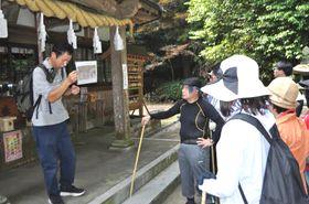 登山道入り口の太歳神社で物怪録との関連について話す吉川代表(左端)